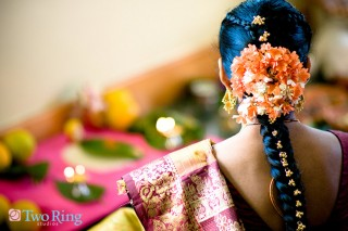 Indian bride faces away showing off her flower adorned, braided hair.