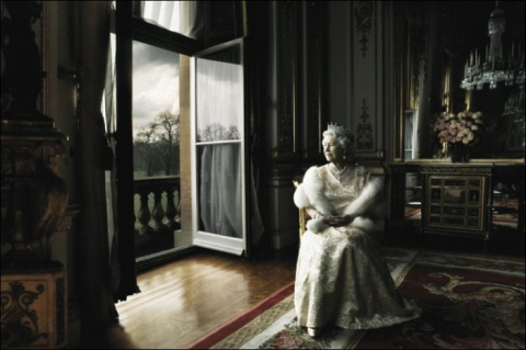 Queen Elizabeth sits in a chair looking out the window