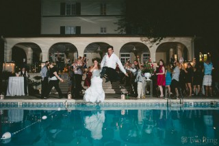 Bride and groom jump in pool